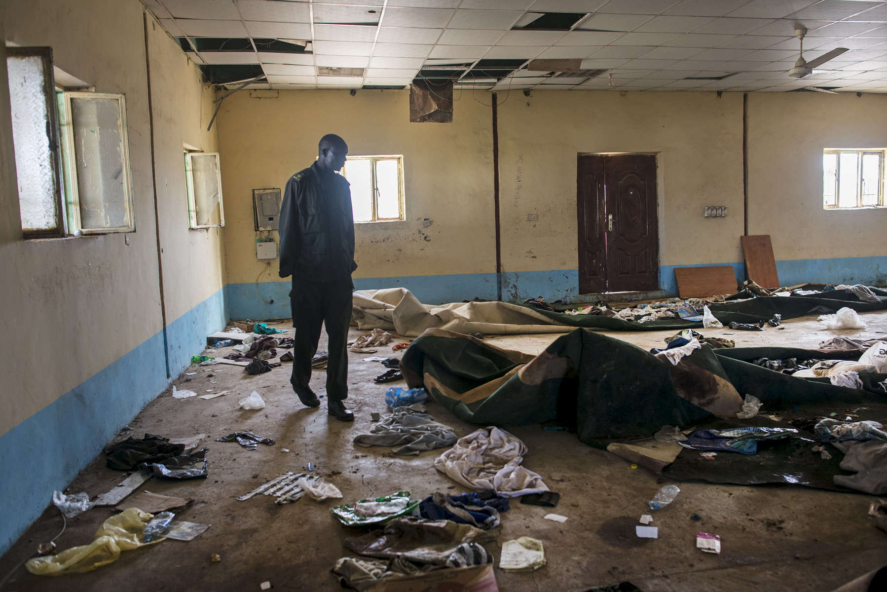 A Nu'er soldier with opposition forces walks through the remnants of clothing, trash, pages for the Koran, and blood left by the massacre at the Kali-Ballee mosque in Bentiu, where hundreds were executed while taking refuge from heavy fighting between government and incoming opposition troops on April 15, 2014 in Bentiu, South Sudan, May 3, 2014.  The scene at the mosque in Bentiu was one of several masacres noted in the recent United nations report documenting human rights atrocities by both the government and opposition forces across South Sudan, where people were routinely killed based on their ethnicity. Over twenty-thousand internally displaced people live at the UNMISS base in Bentiu, and one million Southern Sudanese have been displaced from their homes as the civil war rages in the country, pitting ethnic Nu'er against Dinka.  (Credit: Lynsey Addario)