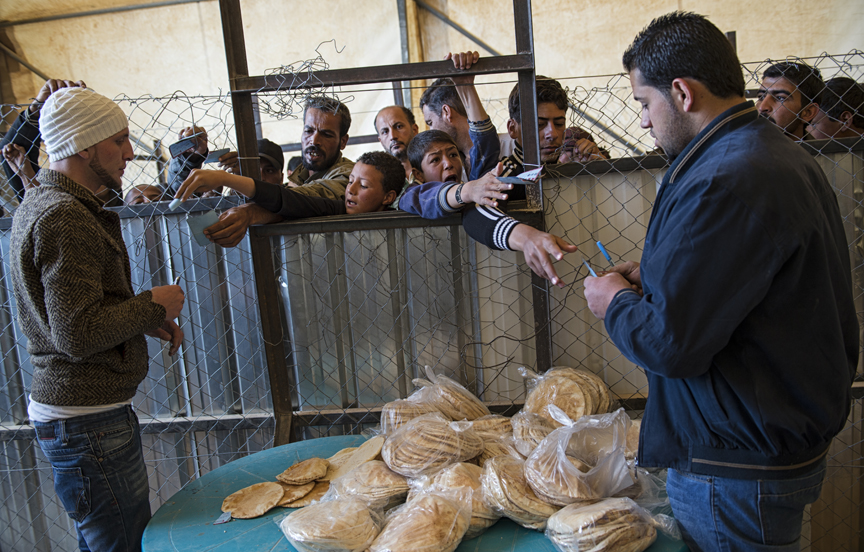 Syrian refugees collect their daily bread ration at a distribution administered by the World Food Program at the Zaatari refugee camp in Jordan, April 8, 2013.  WFP distributes 500,000 pieces of bread each day to roughly 100,000 Syrian refugees living in the camp, and at this particular bread distribution, riots erupt almost daily as the refugees fear they will not receive their bread rations.  As the civil war in Syria enters its third year, a steady stream of civilians continue to flood neighboring countries hrough official and unofficial border crossings as they flee ongoing violence; the United Nations estimates that the number of Syrian refugees is currently over one million.