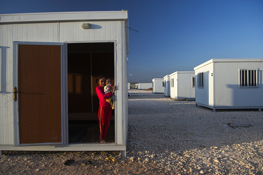 A Syrian girl holds her sister while standing in the door of the trailer alotted to her family earlier that day by the United Nations High Commission for Refugees at the Zaatari refugee camp in Jordan, April 7, 2013.  Roughly 100,000 Syrian refugees live in the camp, and of those, only about 6,000 have been given trailers as opposed to tents.   More and more Syrian refugees arrive each day through official and unofficial border crossings between Syria and Jordan as the civil war in Syria enters its third year.   The United Nations estimates that the number of Syrian refugees living in countries bordering Syria is currently over one million.