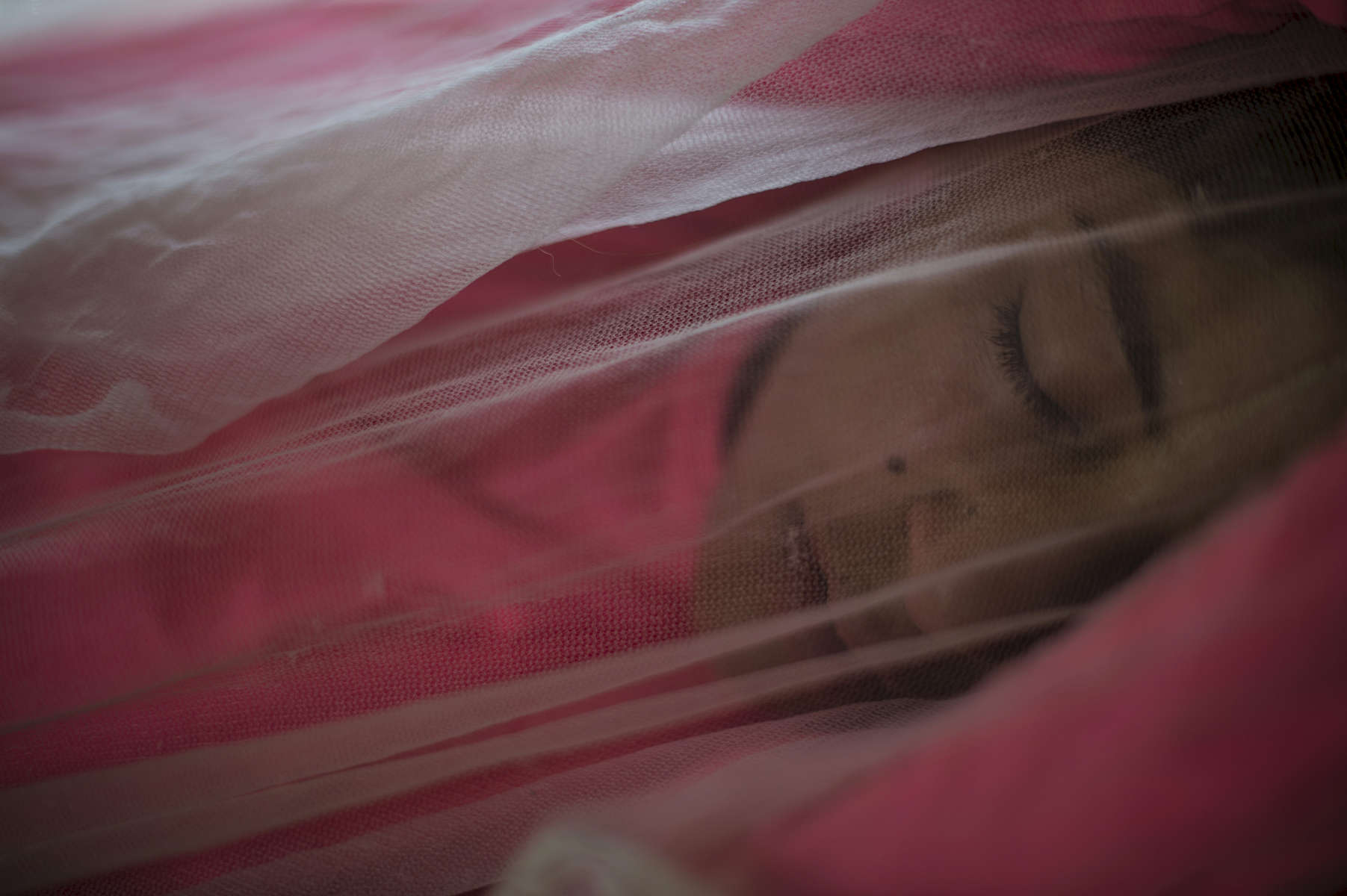 Hanaa takes a nap under a mosquito net in her tent in the informal tented settlement she lives in with her family after a long morning picking cucumbers from dawn with other Syrian refugees,in the Bekaa Valley, between the city of Zahle and Baalbak, in Lebanon, August 1, 2015.  Hanaa and her family fled Syria in 2011 at the beginning of the Syrian civil war, and moved to this settlement two years ago, along with other Syrian refugees from Hasaka and the surrounding areas. Hanaa and other children in the settlement work for up to ten hours a day in agricultural lands owned by Lebanese in the area, and earn the equivalent of $5. per day.