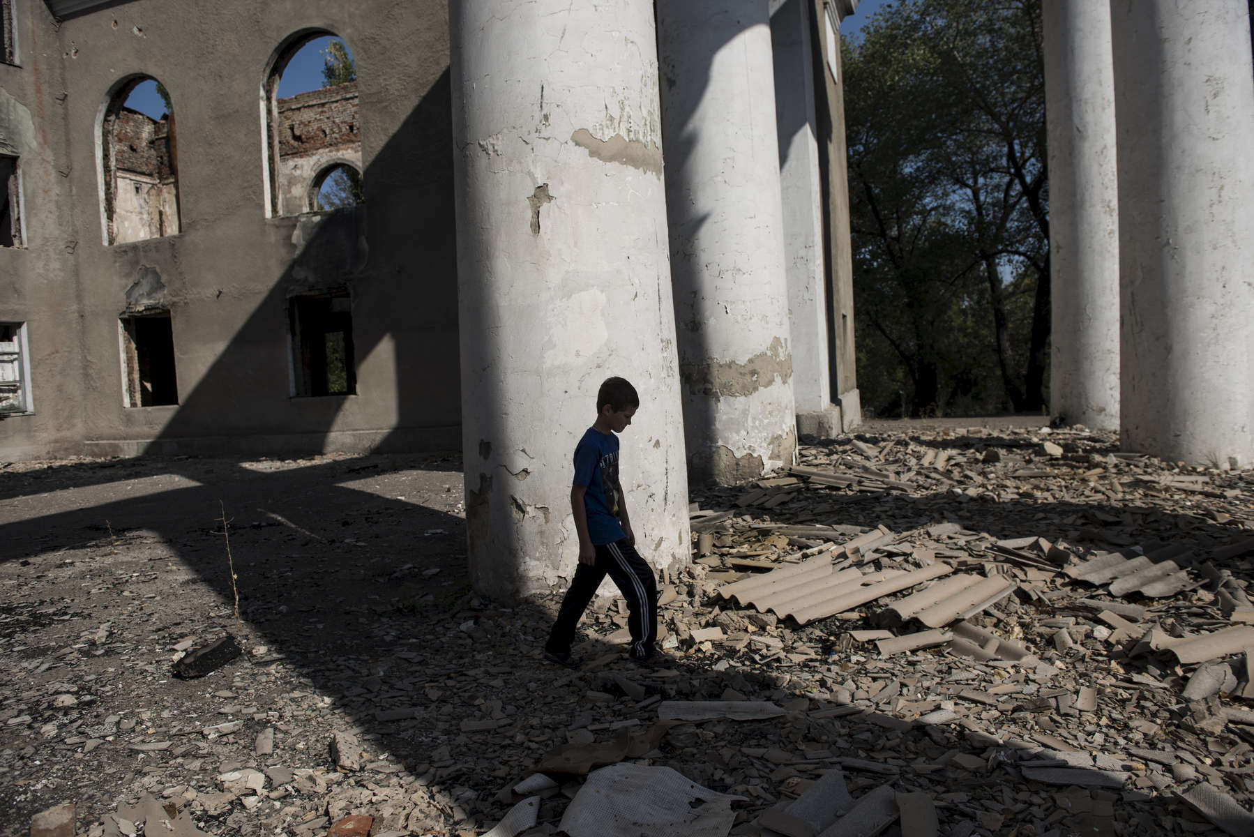 Oleg Teryokhin walks through the remnants of a municipal building in Debaltsevo, the village he and his mother are currently staying in near his native village of Nikishino--both destroyed by the east Ukraine war, September 27, 2015, in DNR territory.  Nikishino village was far from the sites of early skirmishing and neither side bothered trying to control this small village until it turned out it was on the path of a major Ukrainian offensive begun in July with the goal of encircling Donetsk city, the provincial capital. Using long-range artillery and spotter aircraft to target it, the Ukrainian army was pushing separatists back from one town after another. Galina Teryokhina, Oleg's mother, said residents didn't take the war seriously until mid July, 2014. Oleg was playing outside in the afternoon when loud explosions were heard in the sky. Later, some papers with English writing and bits of charred clothes fluttered through the village, and Oleg picked some up. Nikishino village was at the edge of the debris field of the Malaysia Airlines Flight 17, likely shot down by rebels who mistook it for a Ukrainian spotter aircraft.