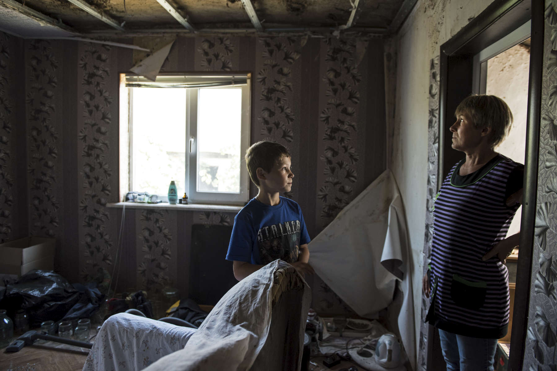 Oleg Teryokhin stands with his mother, Galina Teryokhina, in their home in Nikishino village, destroyed by the east Ukraine war, September 27, 2015, in DNR territory.  Nikishino village was far from the sites of early skirmishing and neither side bothered trying to control this small village until it turned out it was on the path of a major Ukrainian offensive begun in July with the goal of encircling Donetsk city, the provincial capital. Using long-range artillery and spotter aircraft to target it, the Ukrainian army was pushing separatists back from one town after another. Galina Teryokhina, Oleg's mother, said residents didn't take the war seriously until mid July, 2014. Oleg was playing outside in the afternoon when loud explosions were heard in the sky. Later, some papers with English writing and bits of charred clothes fluttered through the village, and Oleg picked some up. Nikishino village was at the edge of the debris field of the Malaysia Airlines Flight 17, likely shot down by rebels who mistook it for a Ukrainian spotter aircraft.