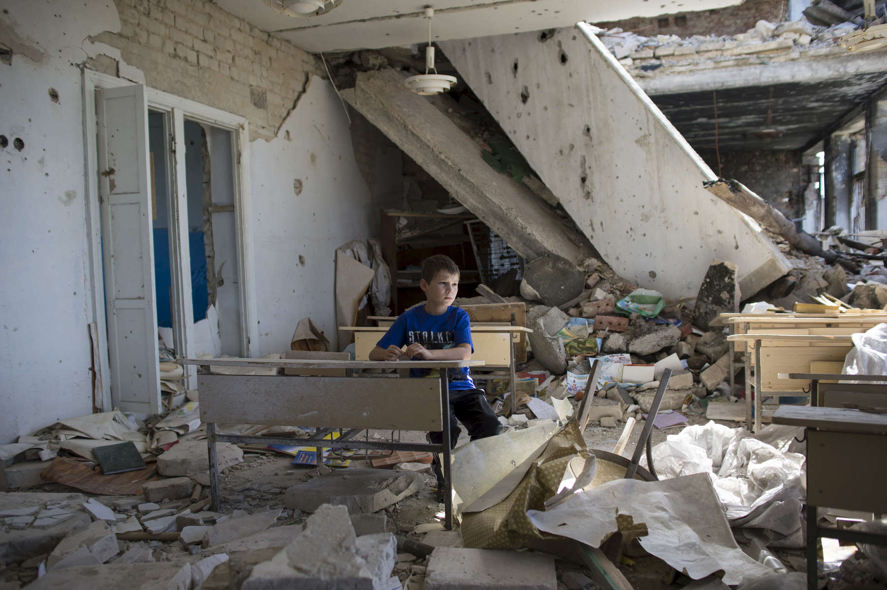 Oleg Teryokhin sits at a desk in one of the classrooms in his former school in Nikishino village, which was destroyed by the east Ukraine war, September 27, 2015, in DNR territory.  Nikishino village was far from the sites of early skirmishing and neither side bothered trying to control this small village until it turned out it was on the path of a major Ukrainian offensive begun in July with the goal of encircling Donetsk city, the provincial capital. Using long-range artillery and spotter aircraft to target it, the Ukrainian army was pushing separatists back from one town after another. Galina Teryokhina, Oleg's mother, said residents didn't take the war seriously until mid July, 2014. Oleg was playing outside in the afternoon when loud explosions were heard in the sky. Later, some papers with English writing and bits of charred clothes fluttered through the village, and Oleg picked some up. Nikishino village was at the edge of the debris field of the Malaysia Airlines Flight 17, likely shot down by rebels who mistook it for a Ukrainian spotter aircraft.