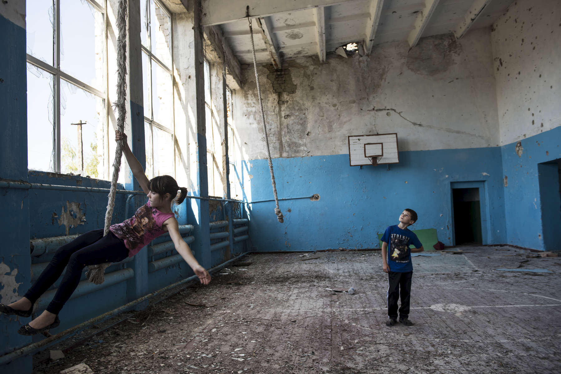 Oleg Teryokhin plays with his cousin, Victoria Pitsul, 13, in the old gym in his former school in Nikishino village, which was destroyed by the east Ukraine war, September 27, 2015, in DNR territory.  Nikishino village was far from the sites of early skirmishing and neither side bothered trying to control this small village until it turned out it was on the path of a major Ukrainian offensive begun in July with the goal of encircling Donetsk city, the provincial capital. Using long-range artillery and spotter aircraft to target it, the Ukrainian army was pushing separatists back from one town after another. Galina Teryokhina, Oleg's mother, said residents didn't take the war seriously until mid July, 2014. Oleg was playing outside in the afternoon when loud explosions were heard in the sky. Later, some papers with English writing and bits of charred clothes fluttered through the village, and Oleg picked some up. Nikishino village was at the edge of the debris field of the Malaysia Airlines Flight 17, likely shot down by rebels who mistook it for a Ukrainian spotter aircraft.