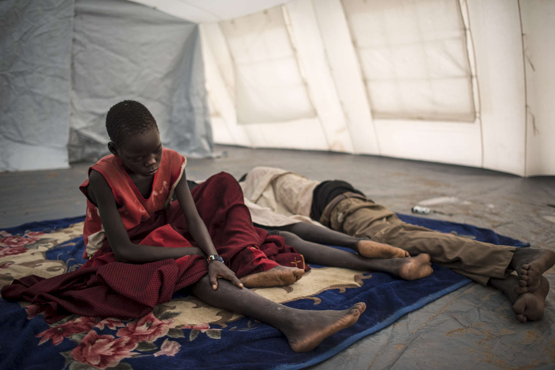 Chuol, 9, from southern Unity State, wakes up in a UNICEF tent school with other internally displaced children in Unity State, South Sudan, September 11, 2015.   Chuol was chased out of his own village with his grandmother and sister several months ago when it  was attacked, and his father and grandfather were burned alive. He, his grandmother, and sister fled to this area, where they are living on the ground of a host family. in South Sudan, September 11, 2015. Thousands of civilians have been killed, and others displaced since fighting between those loyal to President Salva Kiir and those loyal to opposition leader Riek Marchar began again in 2013.