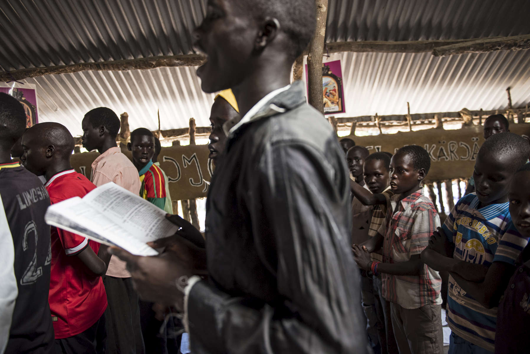 Chuol, 9, from southern Unity State, attends a Catholic mass on a Sunday alongside other internally displaced in Unity State, South Sudan, September 11, 2015.   Chuol was chased out of his own village with his grandmother and sister several months ago when it  was attacked, and his father and grandfather were burned alive. He, his grandmother, and sister fled to this area, where they are living on the ground of a host family. in South Sudan, September 11, 2015. Thousands of civilians have been killed, and others displaced since fighting between those loyal to President Salva Kiir and those loyal to opposition leader Riek Marchar began again in 2013.