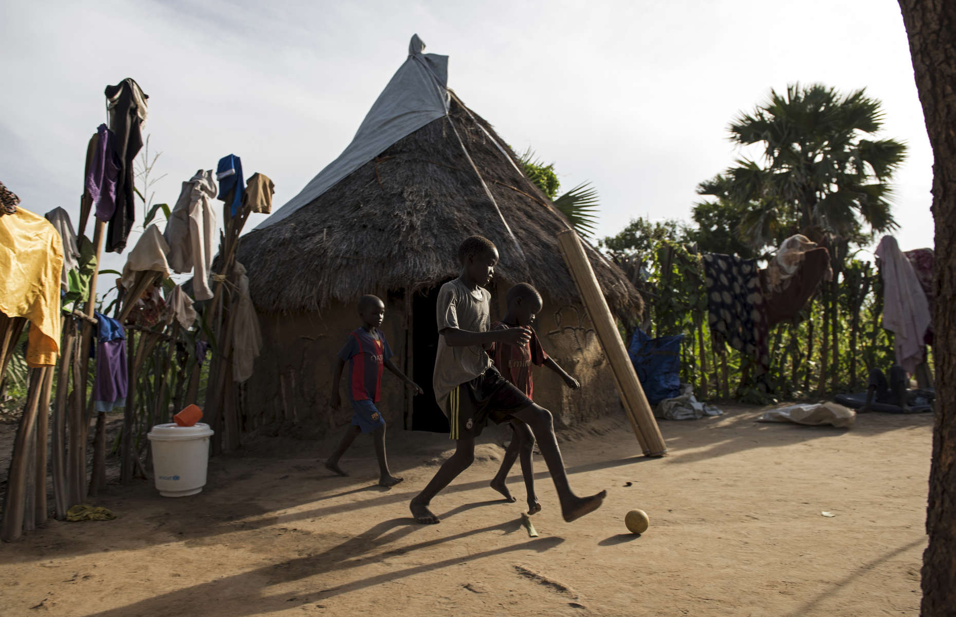 Chuol, 9, from southern Unity State, plays soccer in the compound where he and his relatives are staying alongside other internally displaced Nu'er in Unity State, South Sudan, September 11, 2015.   Chuol was chased out of his own village with his grandmother and sister several months ago when it  was attacked, and his father and grandfather were burned alive. He, his grandmother, and sister fled to this area, where they are living on the ground of a host family. in South Sudan, September 11, 2015. Thousands of civilians have been killed, and others displaced since fighting between those loyal to President Salva Kiir and those loyal to opposition leader Riek Marchar began again in 2013.