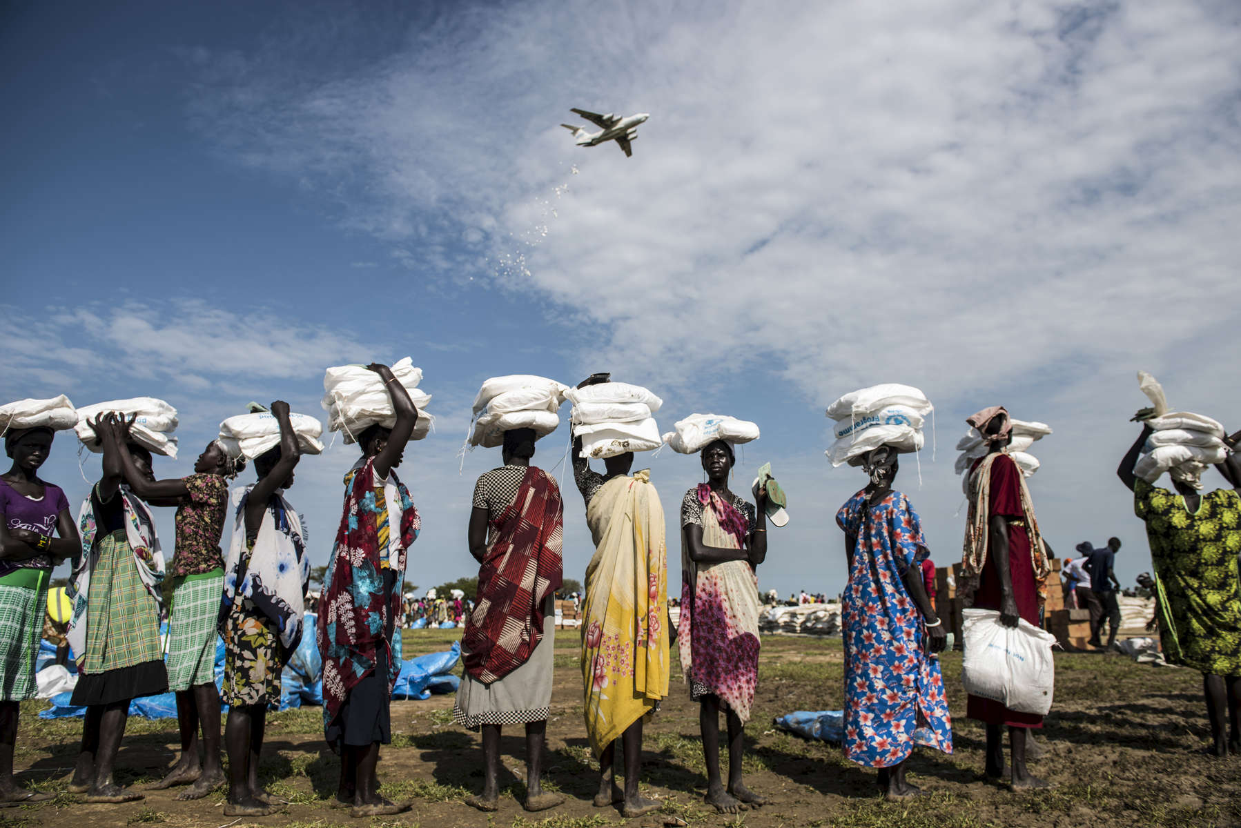 Planes with the World Food Program conduct food drops to help aid new internally displaced Southern Sudanese, who were recently displaced from Leer, Mayangi, and Koch to the  area of Nyal, in Unity State, South Sudan, September 10, 2015.  Because of ongoing fighting throughout South Sudan, civilians have been unable to till their land and plant crops, and aid organisations have been unable to deliver food. In a rare window of peace in the area, WFP has been dropping TK tons of food in Nyal for locals and surrounding villages. Chuol, 9, from southern Unity State or outside Leer, lives within a host community full of local villagers and other internally displaced with his grandmother and sister. several months ago, his own village was attacked, and his father and grandfather were burned alive. He, his grandmother, and sister fled to this area, where they are living on the ground of a host family.