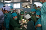 A male Ethiopian surgeon (wearing a green cap, at center left) shows the female staff at Malalai Maternity Hospital in Kabul how to repair a fistula—an abnormal hole between the vagina and bladder or rectum that can lead to infection and incontinence. The condition often occurs during childbirth in young mothers whose pelvises are not fully developed. If the problem isn't corrected with surgery, a woman is typically seen as bringing shame upon the family and is shunned by her husband.