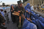 Gulam Farouq, a soldier in the Afghan National Army, hands out bread to Afghan widows and other women outside the shrine to Sufi poet and philosopher Kwaja Abdullah Ansari in Herat. In a country with 35 percent unemployment and 36 percent of people living below the poverty line, Afghan soldiers and police officers typically collect donations from visitors in the area around the shrine and pass them on to the poor and the disabled.