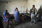 Lance Cpl. Elisabeth Reyes of the U.S. Marine Corps chats with Afghan women and their children at a clinic in Helmand Province, located in the south and considered one of the country's most dangerous areas. She is a member of the relatively new female engagement teams that accompany all-male foot patrols. These teams communicate with, and try to gain the trust of, Afghan women, who are not allowed to speak to men outside of their family in this conservative region. Reyes and other team members helped cordon off part of a clinic in the district of Now Zad to provide separate treatment areas for the sexes.