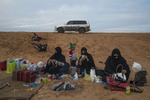 Saudi families picnic in the desert near Janadriya outside of Riyadh, Saudi Arabia, November 29, 2014.   In winter the Saudi tradition of weekend picnics in the desert—with SUVs, multi-course meals, and dune buggies so the men can roar around on the sand—remains popular. Three of the five al Basri sisters relax as their children romp on this slope outside Riyadh. In summer, air-conditioned shopping malls are the public destination most inviting to women and families.
