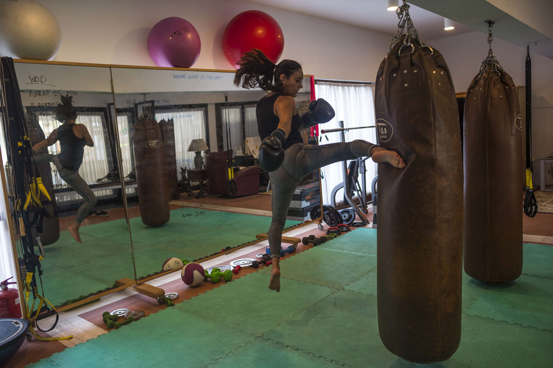 "Saudi women Halal Alhamrani, 38, a kickboxing and boxing instructor and personal trainer trains in her home in Jeddah, Saudi Arabia, December 3, 2014.  Long discouraged from sports, especially those that clerics call masculine, urban women are drawn to clubs and home gyms where they can exercise away from men. Halah Alhamrani, 39, teaches kickboxing at her home in Jeddah; she's a physical trainer, a career that women are taking up despite some hostile response. ""Not just men,"" says another Jeddah trainer. ""A lot of closed-minded women see what we're doing as a disgrace."""