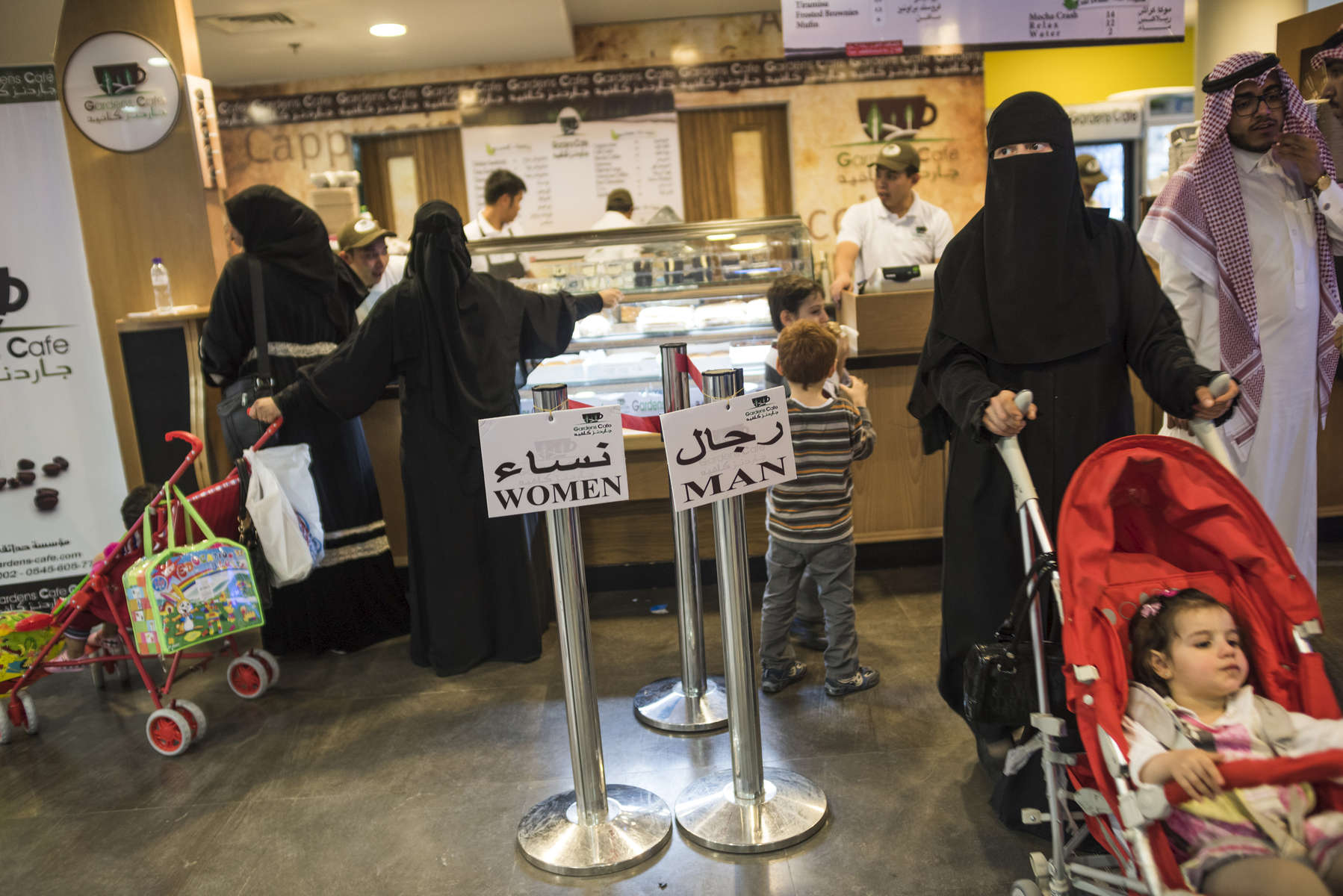 Separation is everywhere- even in line. Food outlets, like this café in Riyadh, must follow unique Saudi laws: All lines, counters, and eating areas are divided to keep unrelated men and women apart, although customers sometimes ignore the signs. Saudi authorities insist, to an extent unmatched in any other Muslim country, that Islam demands this separation in public and that these rules keep society orderly, honor tradition, and show respect for God.