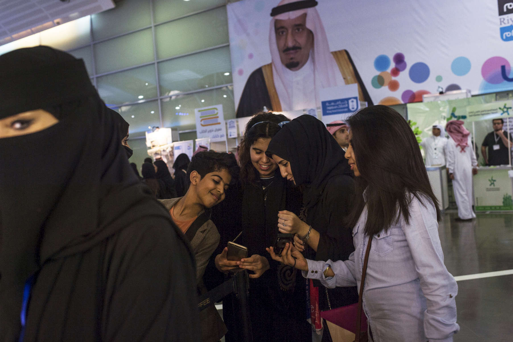 Saudis and foreigners attend the Riyadh Book fair under a banner of Saudi Arabian King Salman at the King Abdullah Conference Center in Riyadh, Saudi Arabia, March 2015.