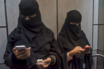 Saudi women check their phones as they ride the elevator at the Stock Exchange to attend a seminar on IT service management in Riyadh, Saudi Arabia, December 1, 2014.