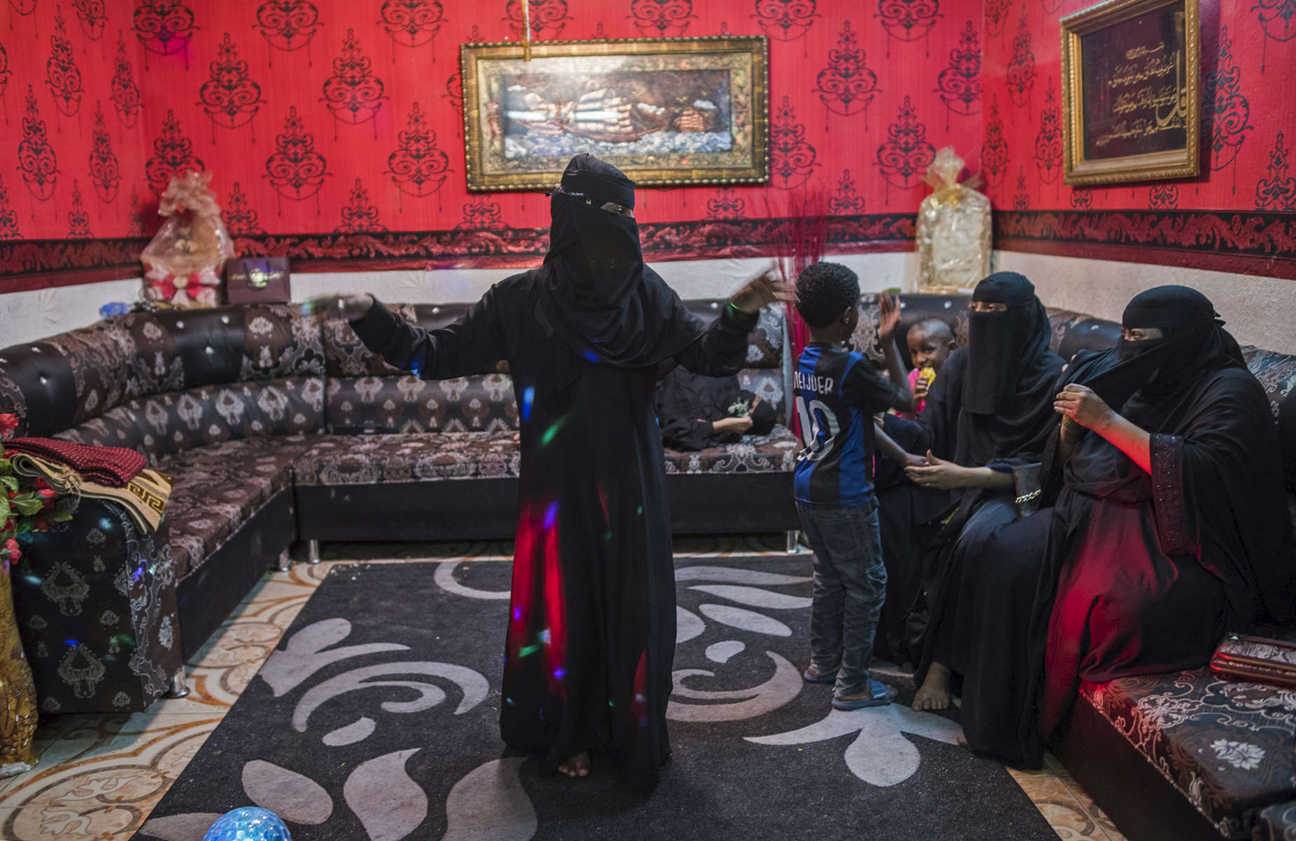 Khadija's son, Ali, dances to American hip hop music as his female relatives watch the day after he returned home from military duty in the eastern province for a vacation in Riyadh, Saudi Arabia, March 20, 2015.