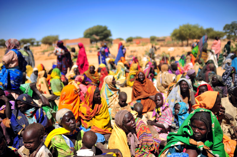 Sudanese women sit and await food and non-food items being distributed by international humanitarian organizations in the village of Selea, which was recently bombed along with two other villages north of Geneina by the Sudanese government and simultaneously attacked by armed men on camels, horseback and donkeys, otherwise known as Janjaweed, in West Darfur, Sudan, February 28, 2008.  The government spate of bombings was in response to an ambush two months prior by rebels from the Justice and Equality Movement, and subsequent intelligence that JEM members were living in these villages and using them as a base. After a period of relative quiet, there has been a great deal of renewed fighting between the Sudanese government with militias loyal to the government and rebel factions, namely JEM. Dozens of civilians in Selean, Sirba, and Abu Sarooj were killed in the attacks around February 8-9th,many others were injured, and a large percentage of each of the three villages was burned to the ground.