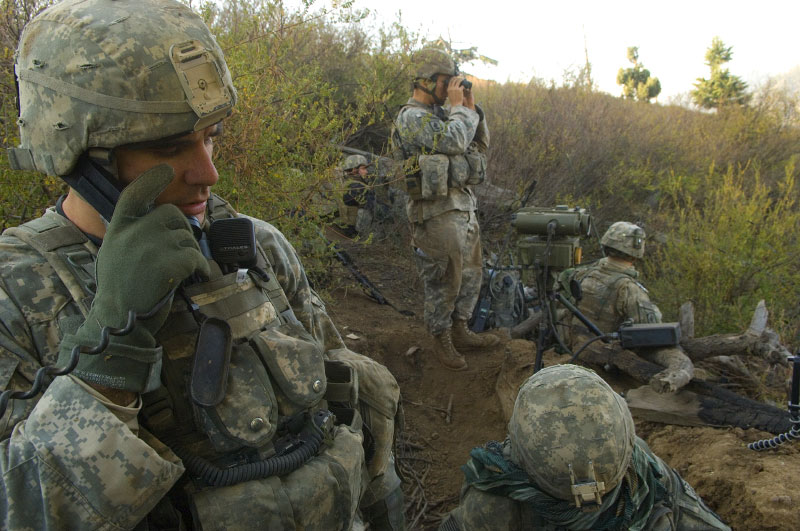 Captain Dan Kearney, with the 173rd Division, Battle Company, speaks with Battalion headquarters as he watches over his troops and controls close air support fire from a ditch above the village with a group of his soldiers and the JTACs while on a battalion-wide mission in the Korengal Valley to find caves, weapons caches, and known anti-coalition members in the area. October 20, 2007.