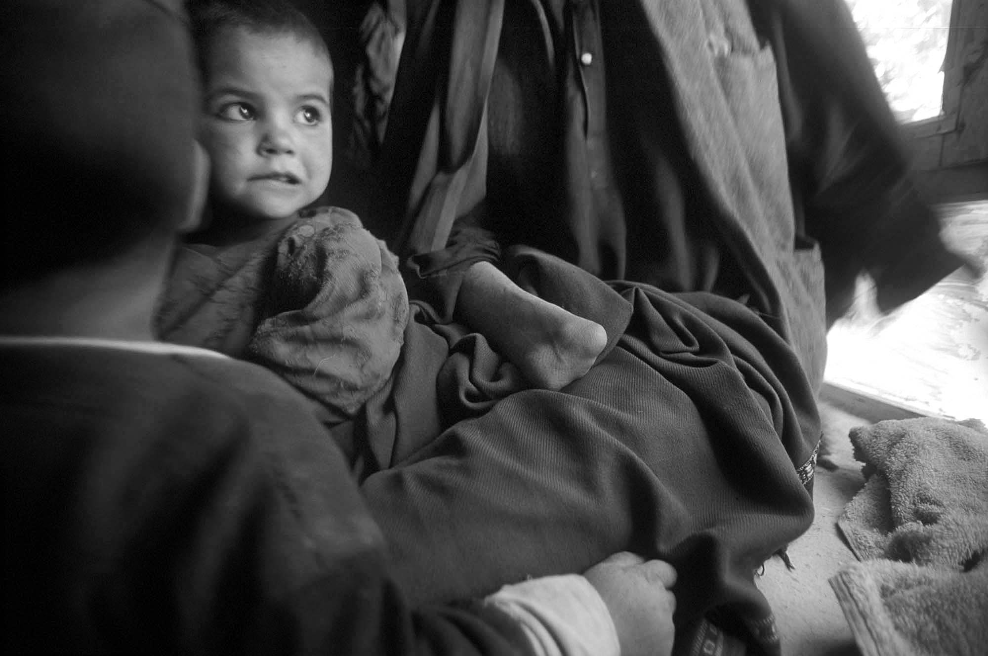Life under the Taliban/ Landmine Victims: Abdullah, a landmine victim, sits with his son and daughter at home in Logar province, Afghanistan, May 2000.  For seven years, Abdullah was involved in fighting on behalf of the mujhideen, and stopped only when he lost both hands and his sight when he leaned on a landmine in an attempted attack on the Russian troops.   He looks at the war now, and thinks {quote}..fighting is totally wrong.  It is worthless--just killing each other.  It increases the number of widows, and the number of disabled.  Abdullah has received vocational training from CDAP, an NGO for landmine victims, and earns minimal money as spends most of his days sitting at home with his children.  Signs of 20 years of war plague Afghanistan's infrastructure and culture and affect every realm of life.