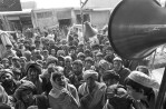Afghan War: Afghans gather around the speakers of a music store on the streets of Kandahar, Afghanistan, December 12, 2001.  Under the formerly ruling Taliban, music was banned for almost six years, and only since they surrended their last stronghold of Kandahar have people come out to the streets to celebrate with music and entertainment.