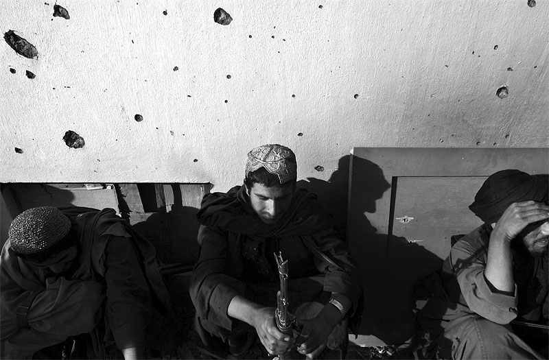 Afghan War: Afghan fighters sit outside of Mullah Omar's residencial compound now being used as Interim Head Government, Hamid Karzai's, headquarters in Kandahar, Afghanistan, December 12, 2001.