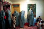 Life under the Taliban: Women put on their burquas as they prepare to leave a secret wedding under the Taliban Regime, Herat, Afghanistan. March 2001