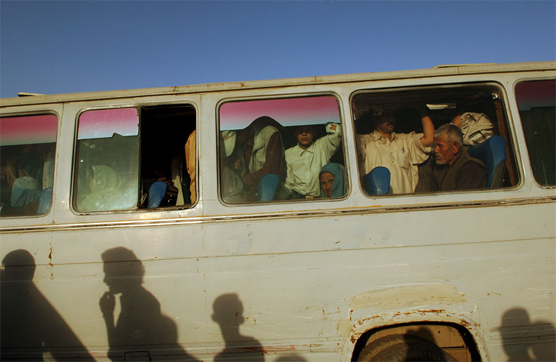 Afghans ride the bus through the main market in Kabul, Afghanistan, August 16, 2005