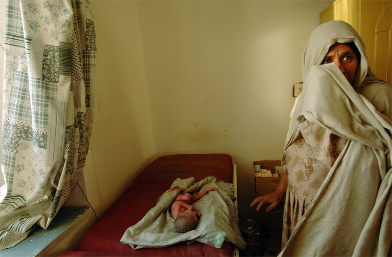 A woman stands beside her premature granddaughter born minutes earlier on the front lawn of a clinic run by Parlimentary Candidate Dr. Roshanaq in Wardak province, Afghanistan, August 22, 2005.  Afghanistan has seen much progress in some areas of infrastructure and human rights, and dismal lack of progress in other areas, as it gears up for its first Parlimentary elections since the fall of the Taliban in 2001.