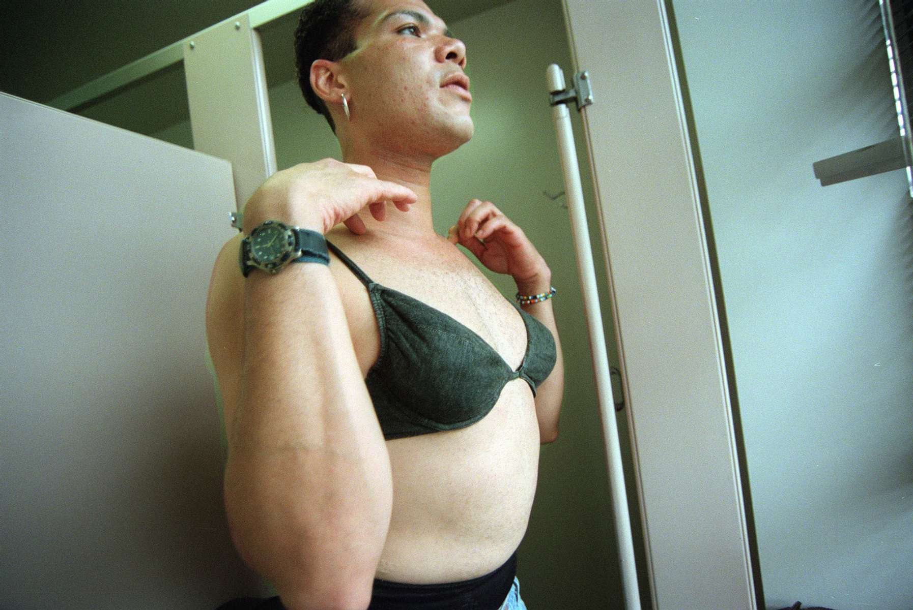 Angel puts on her bra while changing from male to female in a public bathroom at the Gay Man's Health Crisis Center in the West Village's meat-packing district in New York. Angel's step-father does not know she dresses as a woman when out of the house, so he must change in public restrooms. September 1999.