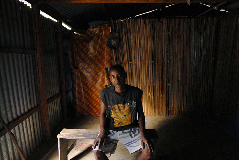 Justin Betombo sits alone in his home he shared with his wife, Lydia, and his neice, Kenia Moravelo, 13, before he allegedly sodomized Kenia one evening when she was 8 years old in their village outside of Sambava, in northeastern Madagascar, November 2, 2006.  Since Kenia accused Justin of rape, the trial has mysteriously disppeared from the courts in the local district head, Antalaha, and Kenia has been in and out of the hospital; Justin's wife, Lydia, left him 8 months ago.  Kenia has been in and out of the hospital and surgery since she was raped, and Justin claims she is suffering from witchcraft.