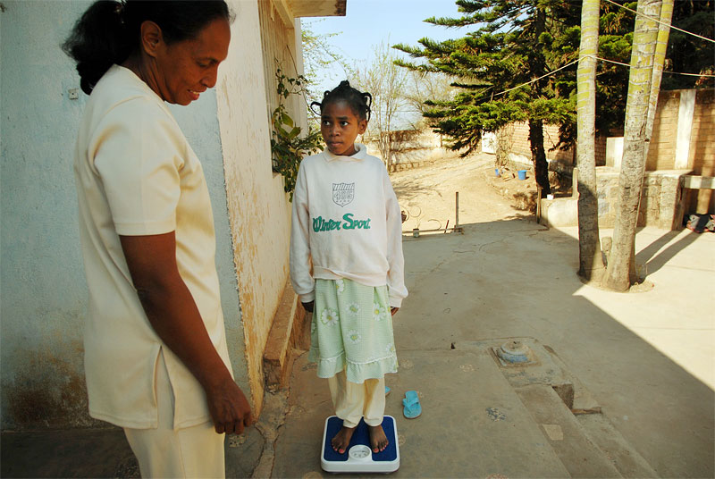 Kenia Moravelo, 13, weighs herself as Dr. Hande looks on at the shelter run by Dr. Hande where she has been staying since released from her most recent stay in the hospital, November 1, 2006, in Antananarrivo, Madagascar.  Kenia was sodomized by her uncle three years prior, and went through several surgeries to try to repair her rectum and colon, which were destroyed in the rape.  Kenia almost completely stopped eating after the rape in order to avoid the pain she endured going to the bathroom, and is only now gaining a little weigh back after years of being extremely thin.