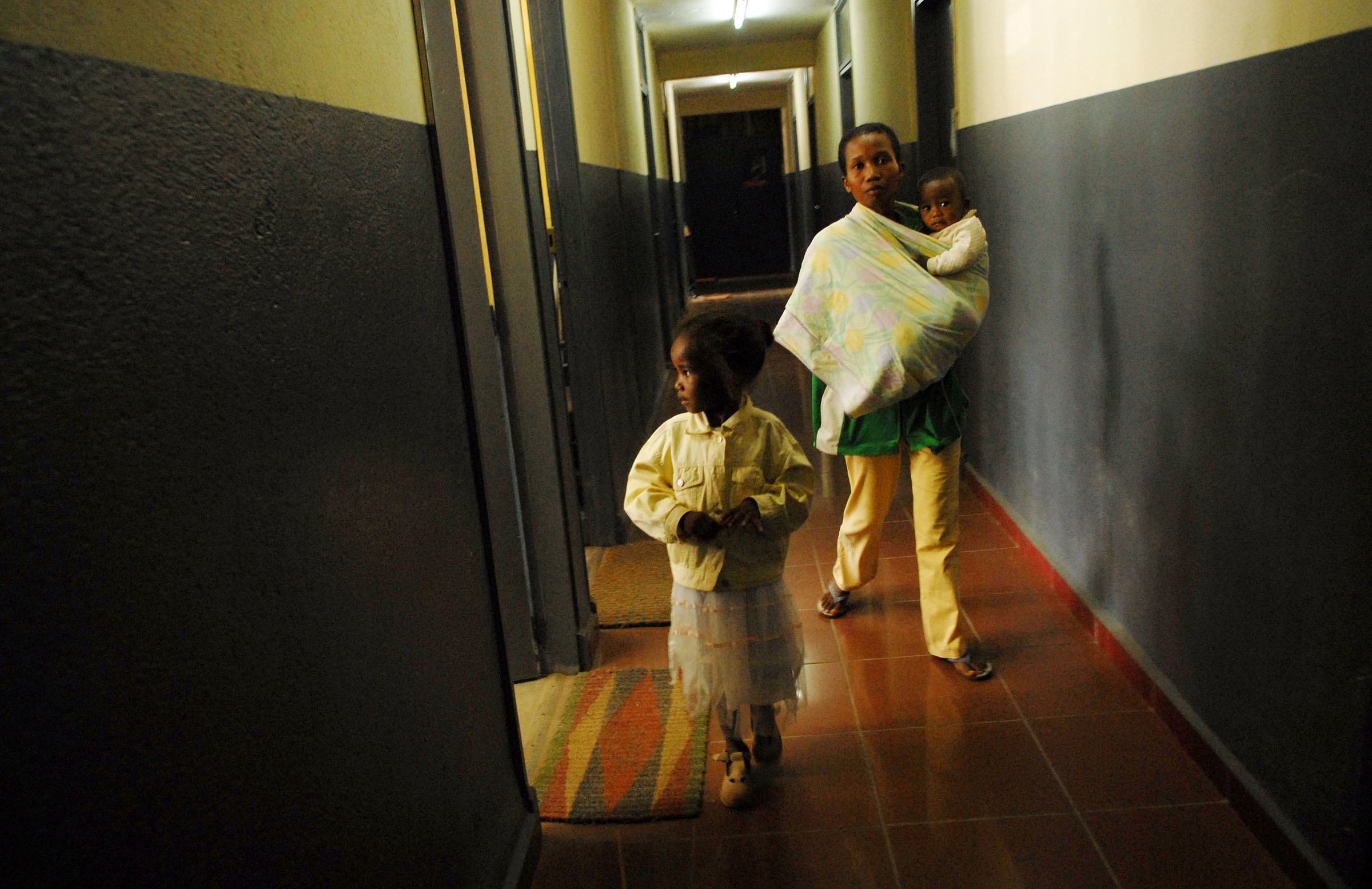 Menja, 5 years old, walks with her mother, Domoina Rahahntanirina, through the halls of the police department while on their way to court to fight a case of sexual assault in Antananivarro, Madagascar, November 9, 2006.  Menja was molested by her uncle one night, and told her mother of the crime, and subseqently identified him in court as the perpetrator. Domoina, who lives with her four children in this one room, did not have enough money to pay the $15. fee for a medical exam for her daughter, facing the same dilemma as many poor Malagassy who do not have enough money to file a case for a victim of sexual assault.  She eventually came up with the money, and the husband of her sister, the perpetrator, is now in jail.