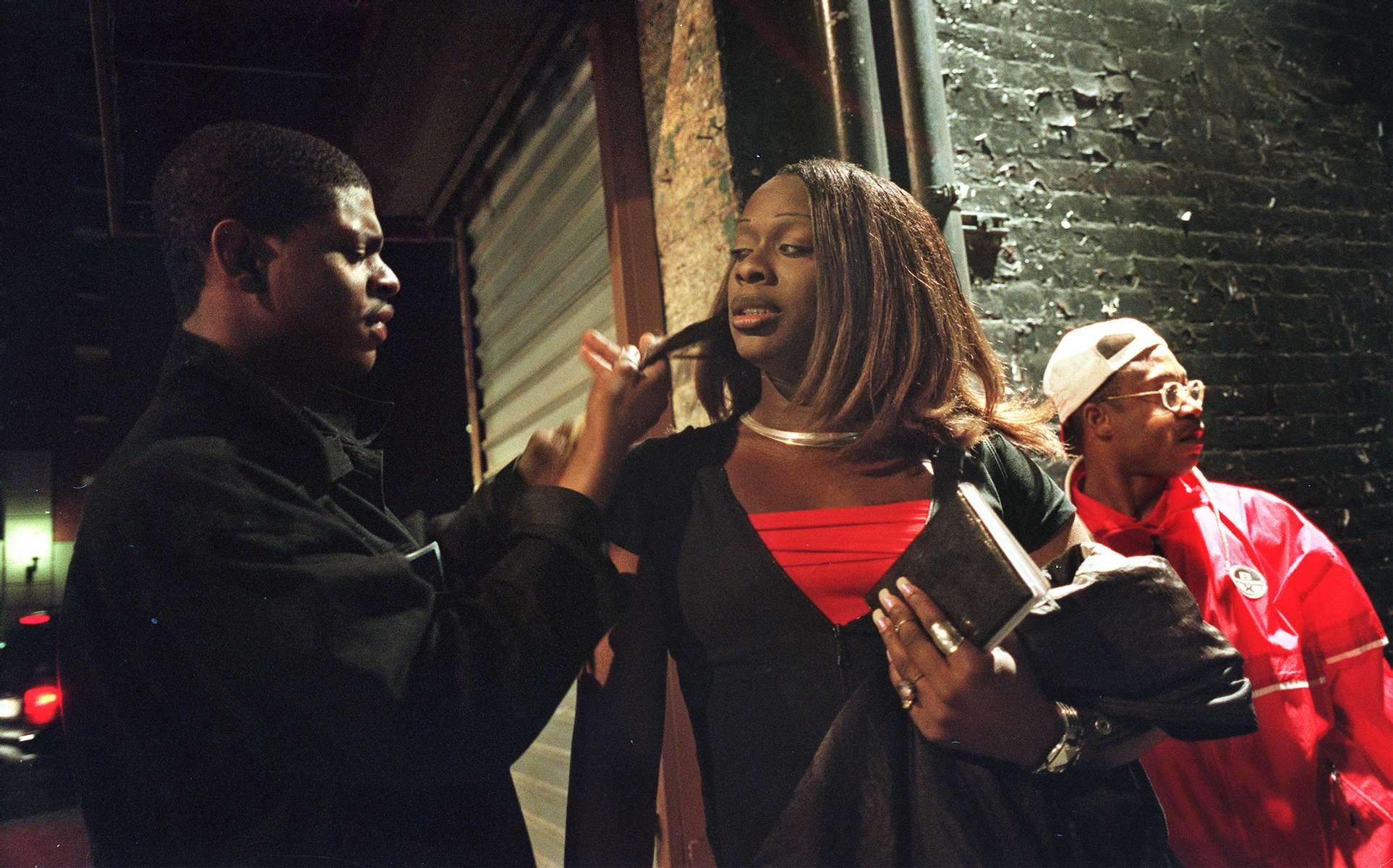Aurora's friend brushes her hair while her ex-boyfriend, Muhammed watches for cops, right, as she pauses between clients in the West Village on Saturday, May 16, 1999.