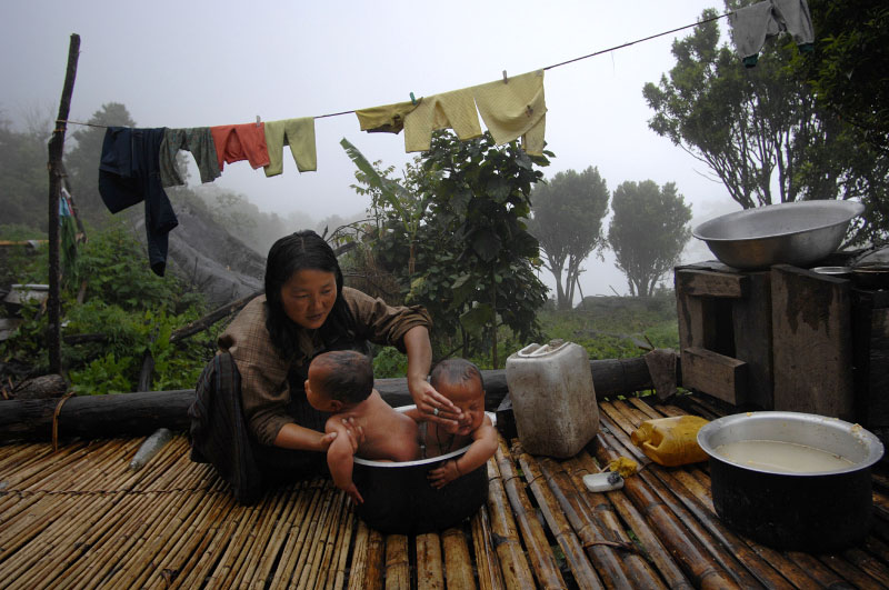 A women washes her child and her sister's child in a pot on their porch in Kudra village in the Jigme Sigme National Park along the Black mountains in central Bhutan.  There are no roads leading through the area, and inhabitants have no electricity, and no running water in their homes--there is often one water pump per several households.  The trail the Jigme Singye park was just opened up to foreigner visitors in 2006, and at the time of this hike, less than 100 foreigners had ever visited the area.  Villages are at least a three to six  hour walk from any road, and enjoy very little influence from the outside world.