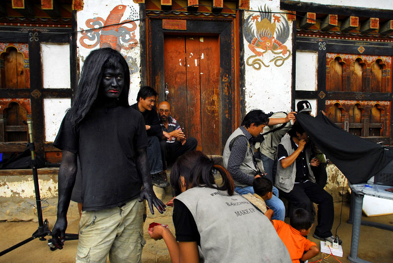 A Bhutanese actor painted as a demon stands next to the director on the set of Bachha, a drama and love story with Bolliwood-style dance sequences, directed by Tshering Wangyel, in Punakha, western Bhutan, August 5, 2007.  Though Bhutanese cinematographers made their first film as late as 1989, roughly 25 films were made in 2006, alone. As Bhutan tries to cater to its own citizens and shy away from being totally dependent on Indian cinema, its film industry is thriving.  Equipment is incredibly basic, and must all be imported from India, and actors and actresses are often forced to prepare their own make-up, but the Bhutanese audience is receptive to local cinema.