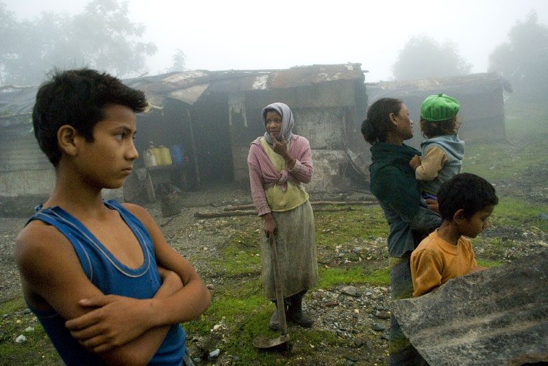 Indian citizens of Nepalese origin stand in front of the corregated shacks they stay in while working on the roads in Bhutan, a job traditionally reserved for Indians and non-Bhutanese citizens, in the village of Ganglakha, in South Bhutan near the Indian border, July 31, 2007.  In the early 1900's Bhutan encouraged Nepali migration to Bhutan, enabling Nepalese work opportunities in the country; as the Nepalese population grew, the Bhutanese elite and ruling class were overwhelmed by the numbers of foreigners, and began to enforce strict cultural assimilation laws, driving the Nepalese to protest and to be marginalized in society. The protests culminated in teh 1980's and 1990's, when eventually many Nepalese were kicked out of the country.  Today, ethnic Indians and Nepalese who are not Bhutanese citizens enjoy employment in building Bhutan's infrastructure.