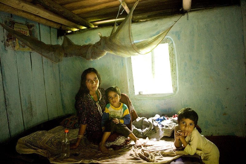 A Bhutanese woman of Nepalese origin sits sick with Dengue fever with her two sons in her home she inherited from the government as part of a resettlement program by the government to redistribute homes abandoned by ethnic Nepalese in the 90s, in Samtse, Bhutan, August 2, 2007. In the early 1900's Bhutan encouraged Nepali migration to Bhutan, enabling Nepalese work opportunities in the country; as the Nepalese population grew, the Bhutanese elite and ruling class were overwhelmed by the numbers of foreigners, and began to enforce strict cultural assimilation laws, driving the Nepalese to protest and to be marginalized in society. The protests culminated in teh 1980's and 1990's, when eventually many Nepalese were kicked out of the country, and their land was resettled to other Nepalese and Bhutanese families.  Today, ethnic Indians and Nepalese who are not Bhutanese citizens enjoy employment in building Bhutan's infrastructure, and small jobs as waiters or as daily laborers, but find it difficult to ascend to higher-paying jobs.