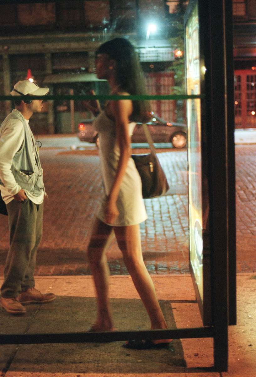 A transgendered prostitute waits for clients at a bus stop in West Village's meat-packing district in New York, August 1999.