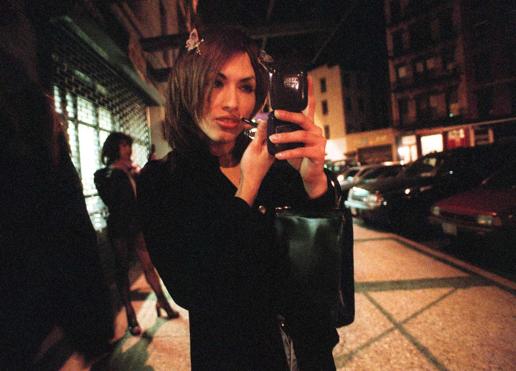 Christian Sosa reapplies her make-up on Little W. 12th Street in New York Sunday morning, April 25, 1999, while other sex workers wait for clients in the background.