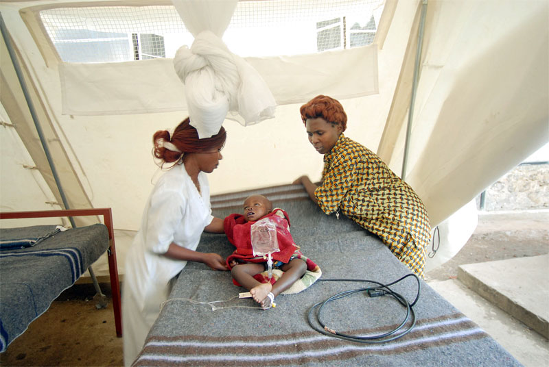Dr. Rose Ange, right, watches Amuri Cheusi, 2 years old, die from lack of oxygen caused by measles minutes after they disconnected him from a respirator in a hospital run by Doctors Without Borders in Rutscuru, in the North Kivu region of The Democratic Republic of Congo, June 16, 2006.  Amuri was sick at home for months before coming to the hospital for treatment, but his family had no means of reaching the hospital, and had no money to pay for treatment.