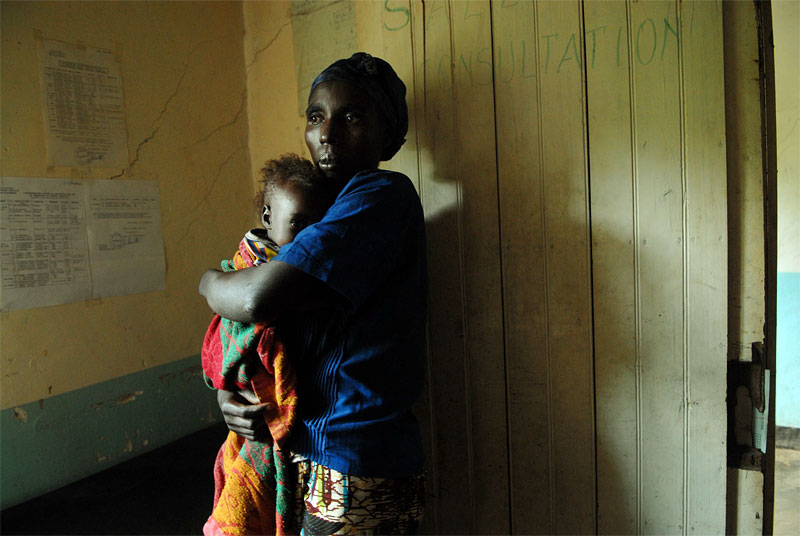 A woman clenches her malnourished daughter while waiting to be transferred with her daughter to a hospital by a medical team attached to Doctors Without Borders on an emergency call in a village near Rutshuru, in the North Kivu region of The Democratic Republic of Congo, June 15, 2006.