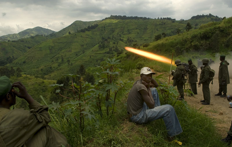 Villagers look on as the Congolese Army fires artillery at rebel soldiers under Congolese Tutsi rebel leader, Nkunda, from the village of Lushangi the morning after the Congolese military took the village of Mushake from Nkunda, in the east of the Democratic Republic of Congo, December 5, 2007. The Congolese army has been making a huge military push in recent days to take back territory that had fallen to rebel soldiers over the past year, and has been successfully pushing forward, and today gained the strategic town of Mushake. In the last 12 months, about 410,000 Congolese civilians have been displaced by new fighting, and coupled with the previous 400,000 from past years, there are now about 800,000 internally displaced people in the DRC.  (Credit: Lynsey Addario for The New York Times)