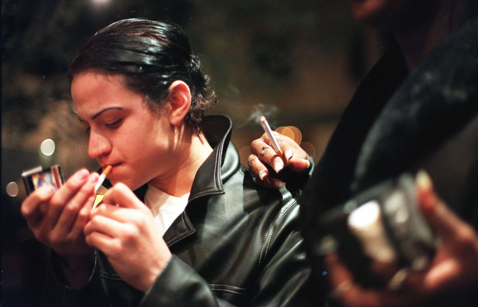 Jamie lights a cigarette while working  alongside Aurora in the West Village's Meat-packing district in New York, April 1999.  Jamie, at 14 years old, is one of the youngest sex worker and is gradually making the transition from male to female. Though Jamie always slicks his hair and plucks his eyebrows, he still wavers between dressing like a boy and a girl, and is quite influenced by the other trans women in the Village.
