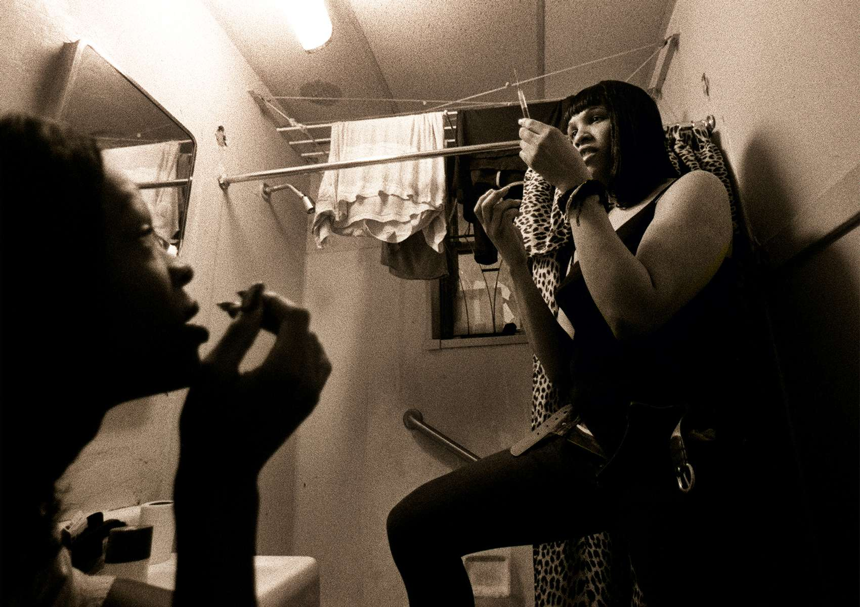 Kima prepares a shot containing 1 cc of Delestrogen and 5cc of Vitamin B12 for Charisse as Charisse looks on in Kima's bathrrom in Harlem Wednesday afternoon, December 1, 1999.  Kima and Charisse buy the hormones on the black market, and take 1 cc of Delestrogen every two weeks via muscular injection. It helps smooth skin, increase body fat, make the body more curvaceous.  The noted side effects are cramping, headaches, occasional fever, and liver damage.