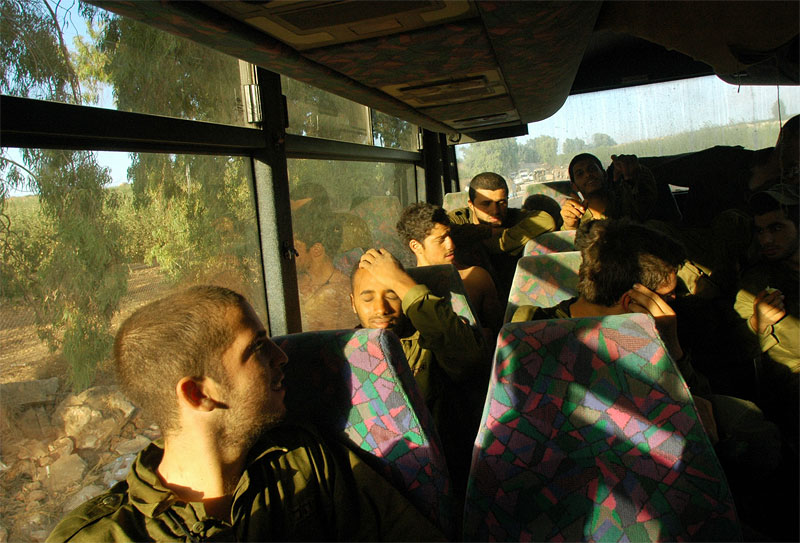 Israeli soldiers sit on a bus  along the frontline in Northern Israel after coming out of fighting with Hizbollah fighters in Southern Lebanon, at dawn, July 28, 2006.  Israeli soldiers are bing wounded and killed daily as fierce fighting continues and the war moves into its third week.
