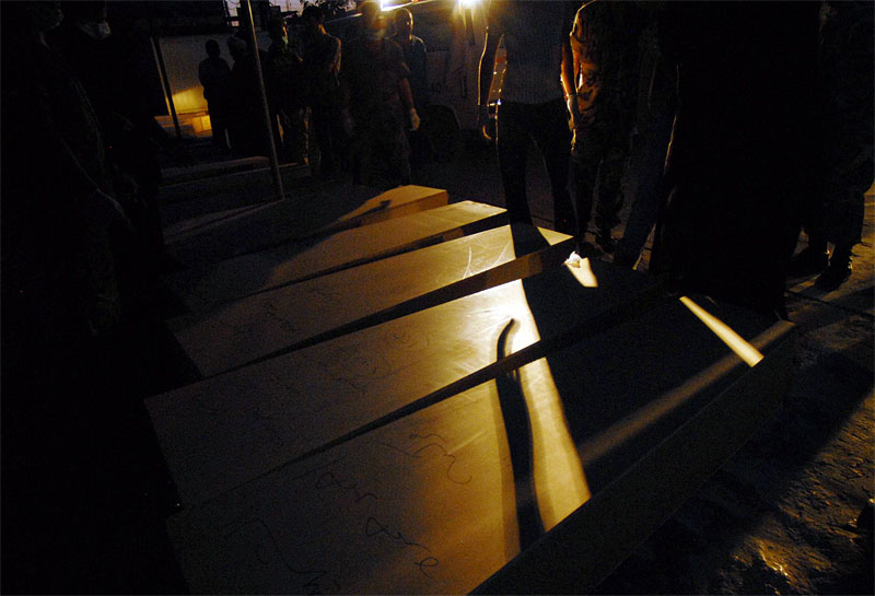 Lebanese soldiers line up coffins at the hospital before a mass burial after amassing uncollected bodies from around the villages of South Lebanon in Tyre, August 15, 2006.   Emergency workers and volunteers began the grim process of unearthing the dead as the second day of theceasefire unfolded.