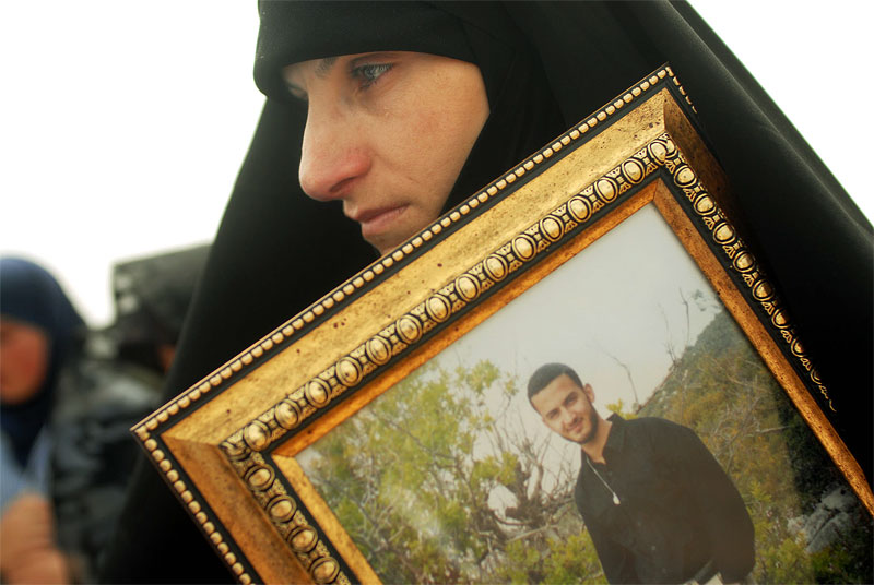 A Lebanese woman weeps quietly as she holds the photo of a Hezbollah fighter during a funeral for two Hezbollah fighters, a two year old child, and an old man, in the village of Shemaa in Southern Lebanon, August 20, 2006.  As burials around the South continue, many villagers are too scared to return to their homes save for a funeral because Israeli troops are still in the area as part of the ceasefire agreement until international troops arrive.