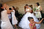 Sanaa Farhat, 26, greets friends and family outside of her home during her wedding ceremony of Israeli Arabs in Majd al Kurum village along the Lebanese border, in Israel, July 22, 2006. Life goes on in this primarily Muslim village as rockets continue to fall in the area and fighting persists inside Southern lebanon.
