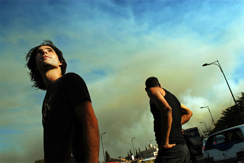 Israelis look up at the smoke billowing across the sky after Hizbollah rockets set fire to patches of countryside near Kiriyat Shmona, in Northern Israel, July 24, 2006, in Israel.  Civilians on both sides of the war continue to die as Israeli troops continued their air and ground assault across Lebanon and Hizbollah fighters continue to send rockets into Israel.